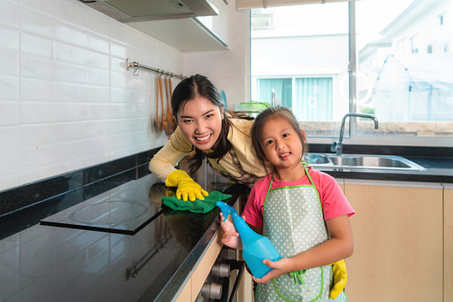 Mom and child cleaning the kitchen after cooking.