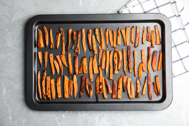 Freshly baked sweet potato fries lined  on a baking sheet