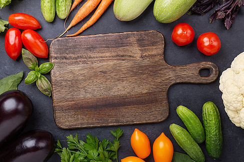 Wooden cutting board surrounded by vegetables.